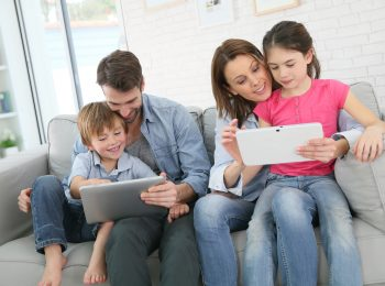 Family of four playing with digital tablet at home