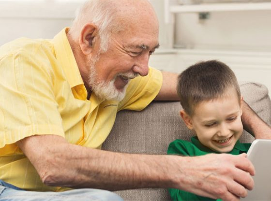 Kid enjoying screen time with grandfather